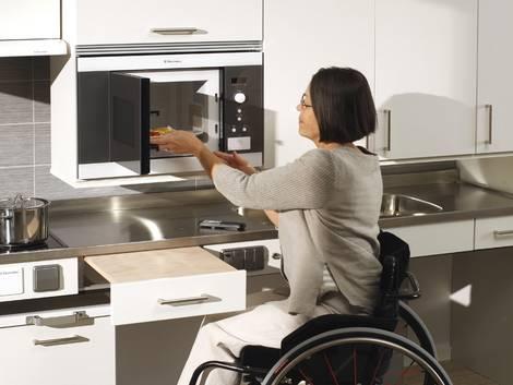 barrierefrei bauen, Küche, Frau im Rollstuhl bedient Mikrowelle, Foto: Granberg GmbH