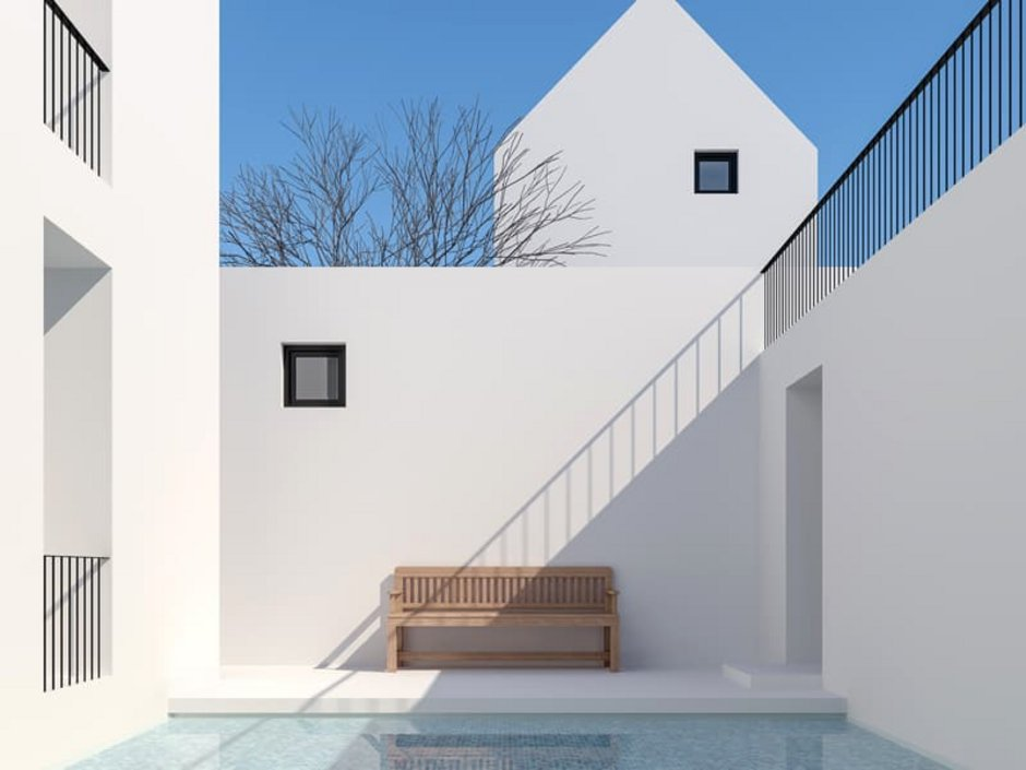 Atriumhäuser, die Wände des Atriums sind weiß gestrichen, der Boden ist auch weiß, ein Naturholzbank bildet einen Kontrast, Foto: iStock.com / runna10