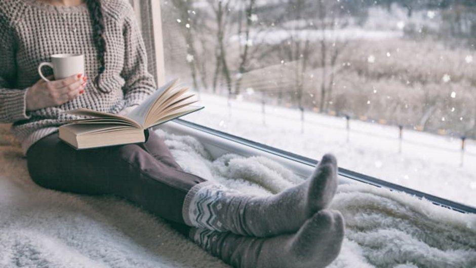 Isolierverglasung, Frau am Fenster mit Tasse und Buch, draußen schneits, Foto: NinaMalyna / stock.adobe.com