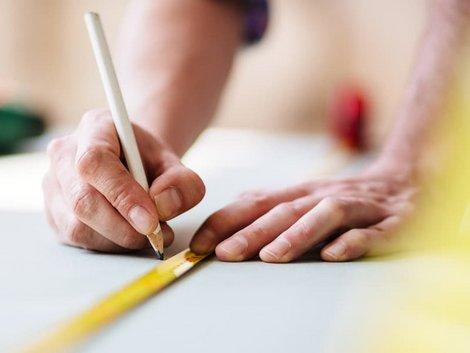 Laminat selbst verlegen, Handwerker misst Raum mit Metermaß aus, Foto: iStock / TommL
