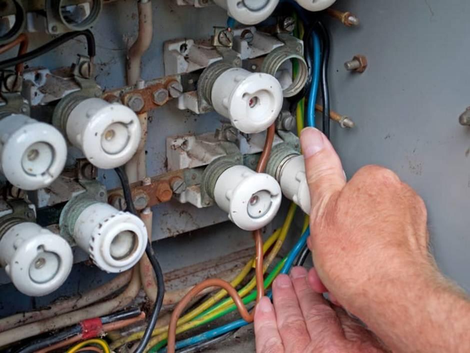 Elektroinstallation, Sicherungsschrank, jemand dreht eine Drehsicherung in die Fassung, Foto: M. Schuppich / stock.adobe.com