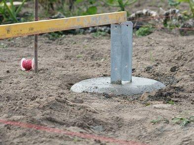 Carport bauen, mehrere einbetonierte H-Träger werden mit einer Wasserwaage ausgerichtet, bevor der Beton aushärtet. Foto: giopixel / stock.adobe.com