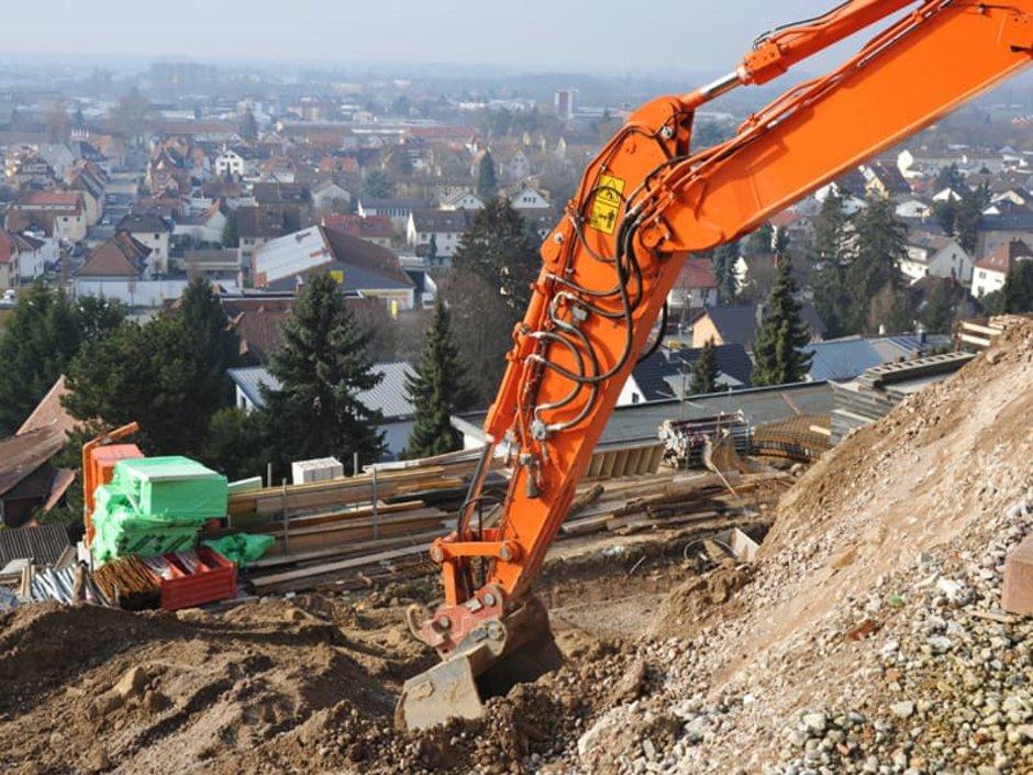 Grundrisse, Baggerarm reicht tief in eine zum Tal hin offene Baugrube hinab. Foto: Hermann / stock.adobe.com
