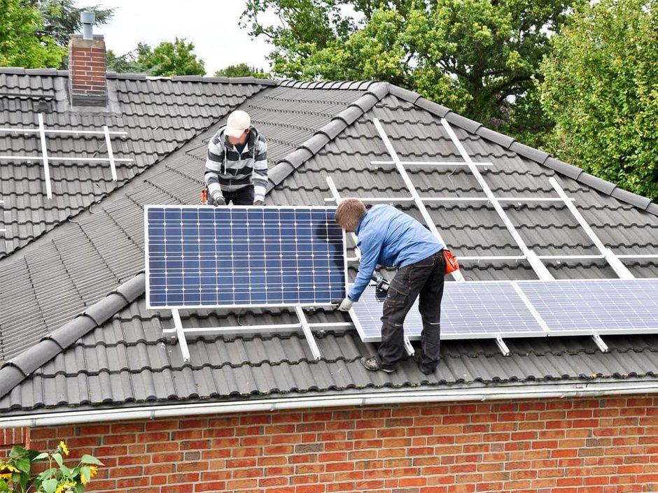 Förderungen, Männer bringen eine Photovoltaikanlage auf dem Dach an, Foto: Marco2811 / stock.adobe.com