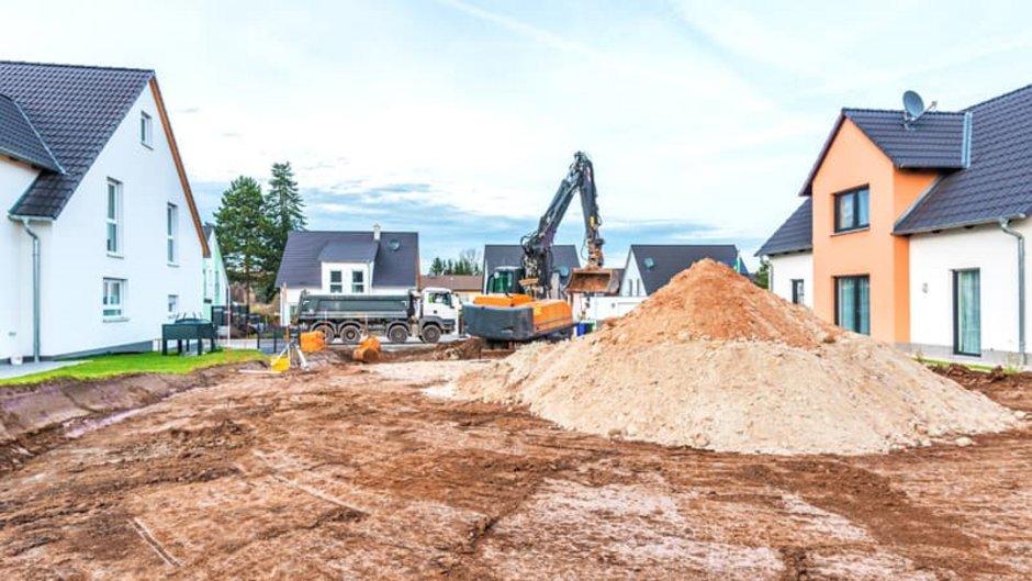 Erdarbeiten, Baustelle in einem Neubaugebiet, ein Bagger hebt die Baugrube aus, Foto: schulzfoto / stock.adobe.com