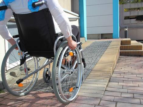 barrierefrei bauen, Person mit Rollstuhl vor Rampe, die zu eine Tür führt, Foto: RioPatuca Images / fotolia.de