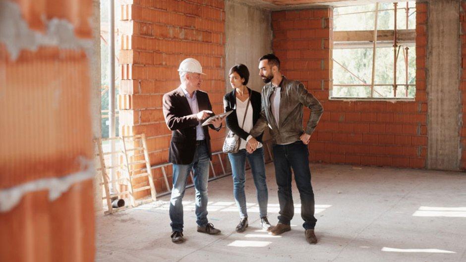 MaBV, Bauherrenpaar im Gespräch mit Bauträger im Rohbau, Foto: iStock.com / diego-cervo