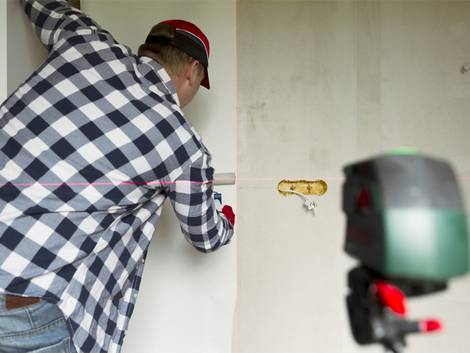 Tapezieren, Mann richtet Tapete mithilfe eines Lasers aus, Foto: artursfoto / iStock