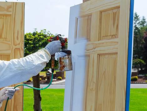 Türen streichen, Handwerker mit weißer Schutzkleidung spritzt Holztür weiß an, Foto: photovs / iStock