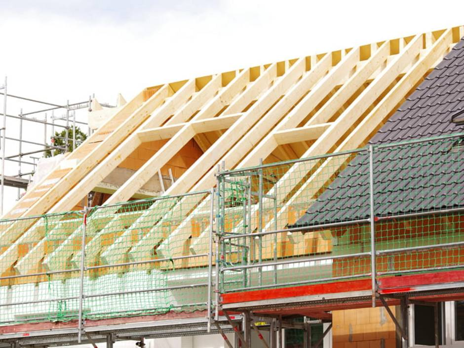 Dachstuhl, Dachstuhl selbst bauen, Rohbau mit Dachstuhl, beim Nachbarhaus ist das Dach bereits eingedeckt, Foto: Wellnhofer Designs / stock.adobe.com