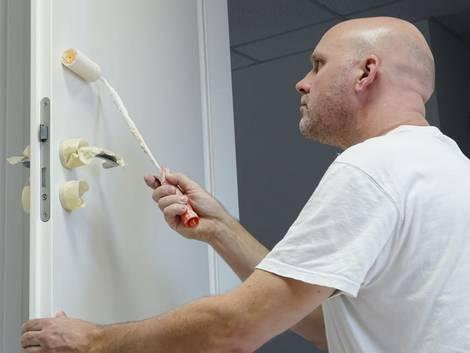 Türen streichen, Mann streicht Tür mit Farbroller weiß an, Foto: Heiko Küverling / stock.adobe.com