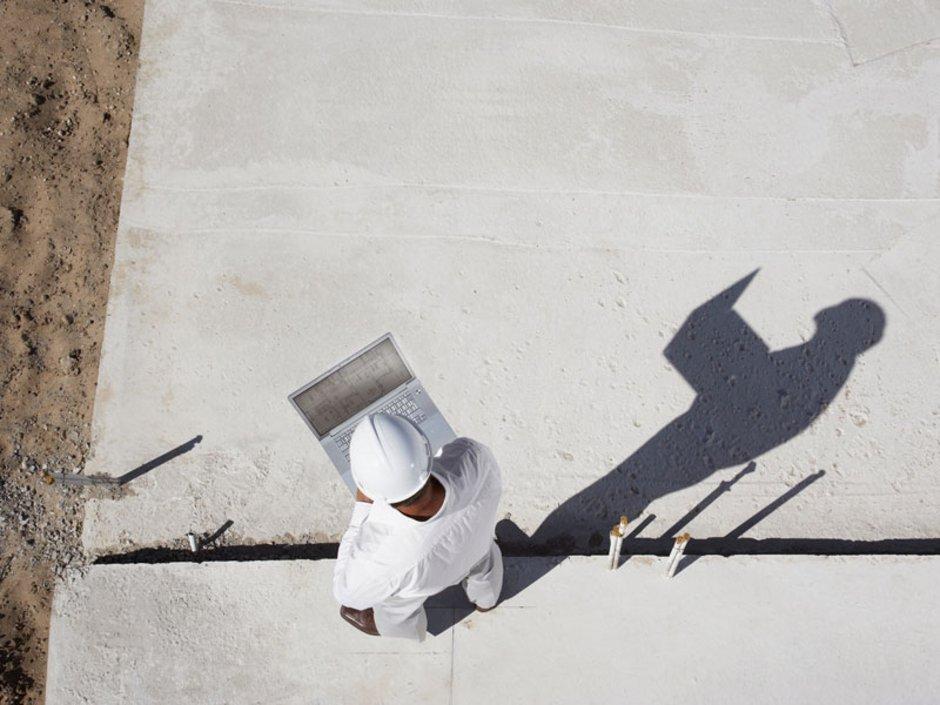 Ein Bauarbeiter mit Tablet auf der Baustelle