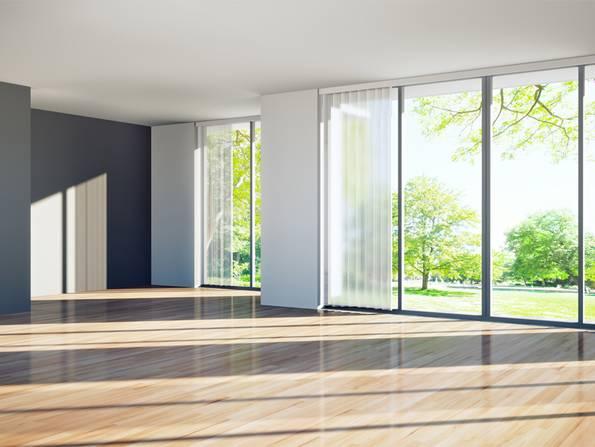schlüsselfertig bauen, das Wohnzimmer eines modernen Neubaus mit Aussicht auf eine Grünanlage, Foto: peterschreiber.media / fotolia.de