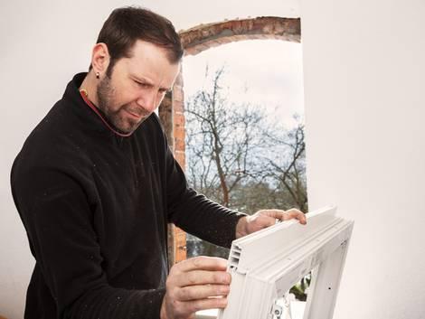 Fenestereinbau, Mann untersucht neues Fenster, Foto: Ingo Bartussek / fotolia.de