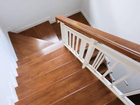 Treppenbau, DIN 18065, Holztreppe mit weißem Geländer und seitlichen Wangen. Foto: stock.adobe.com / sutichak