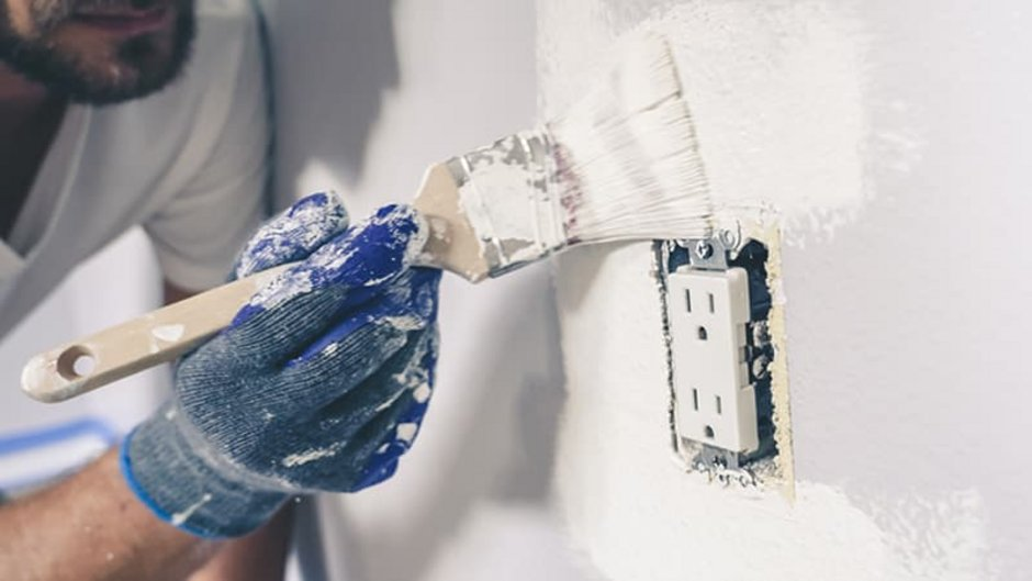 Silikatfarbe, Maler streicht Wand rund um Steckdose mit Pinsel in Nahaufnahme, Foto: iStock.com / RightFramePhotoVideo