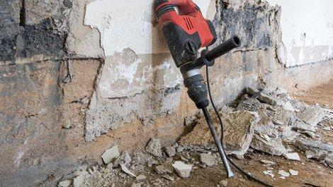 richtig bohren, Bohrhammer mit Meißelaufsatz lehnt an einer Wand, von der der Putz geschlagen wird. Foto: mhp / stock.adobe.com