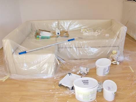 Decke streichen, zu streichendes Zimmer in dessen Mitte ein Soga steht, das mit Folie abgedeckt wurde. Foto: Svenni / stock.adobe.com