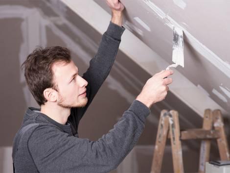 Leichtbauwand, Trockenbauwand, Mann spachtelt Gipswände an einer Dachschräge zu. Foto: Wellnhofer Designs / fotolia.de