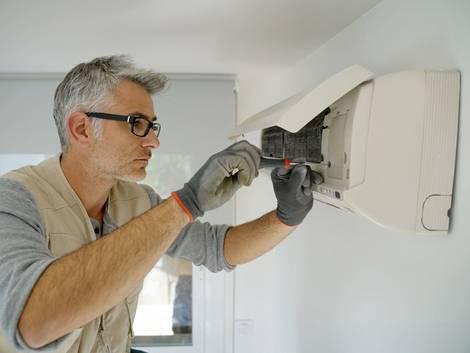 Klimaanlagen, ein Handwerker wirft einen Blick in eine Klimaanlage, Foto: goodluz / fotolia.de