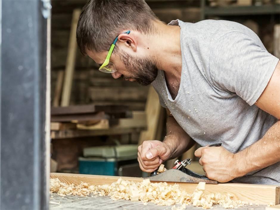 Werkstatt einrichten, Mann hobelt Stück Holz, Foto: Виталий Сова / fotolia.de
