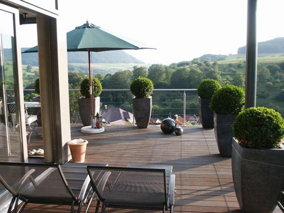 Bauen am Hang, große Terrasse mit Liegestühlen und kleinen Buchsbaumbüschen, Blick ins Tal, Foto: Sawall Architektur