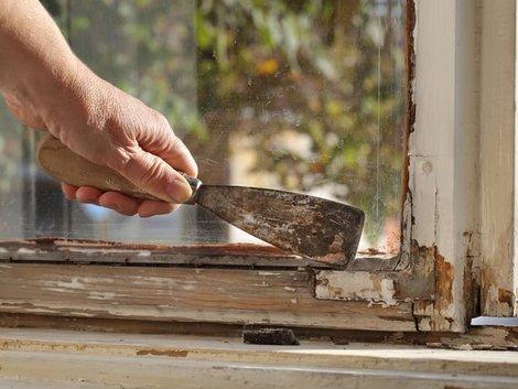 Holzfenster streichen, Heimwerker entfernt alten Lack mit einem Spachtel, Foto: sima / stock.adobe.com