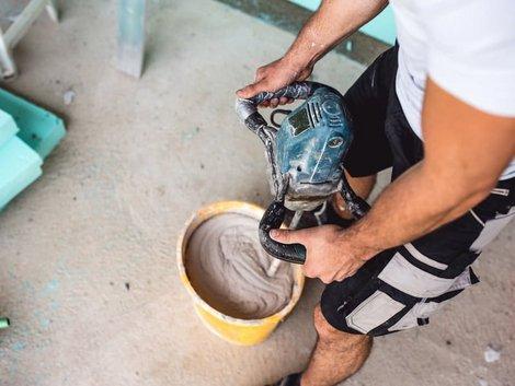 Wand verputzen, Heimwerker rührt Putz in Eimer mit Maschine an. Foto: iStock.com / Pankration