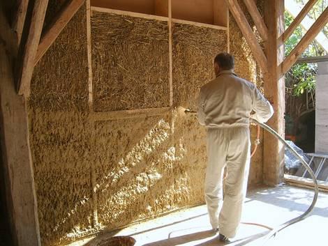 : Ökohaus, ein Mann vor einer mit Stroh gedämmten Wand  in einem Rohbau. Foto: Herbert Gruber/Baubiologie