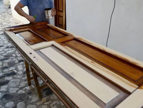 Türen streichen, Handwerker lasiert liegende Tür mit Pinsel und brauner Lasur, Foto: Gangis_Khan / iStock