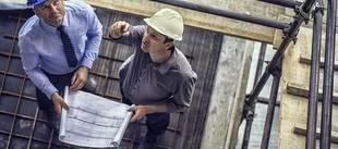 Generalunternehmer, Männer mit Schutzhelm und Bauplan auf Baustelle, Foto: vm / iStock