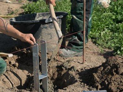 Carport bauen, zwei Arbeiter betonieren einen H-Träger ein, Foto: giopixel / stock.adobe.com