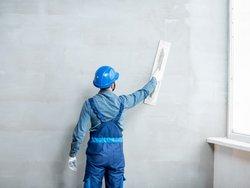 Wand verputzen, Handwerker glättet frisch verputzte Wand, Foto: iStock.com / RossHelen