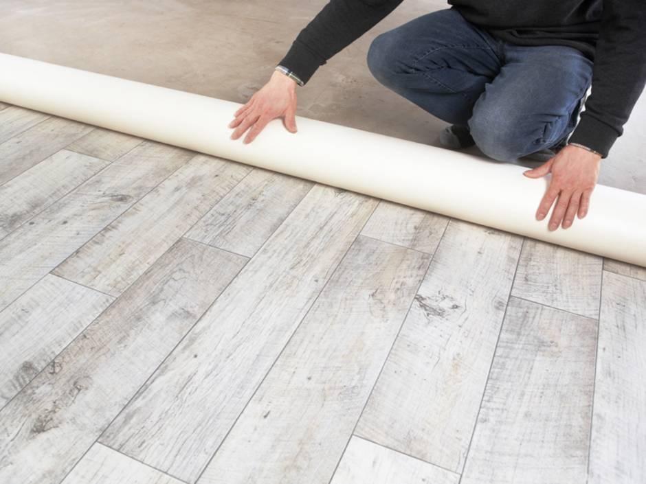 Holzoptik, Handwerker rollte Vinylboden aus, Foto: Ingo Bartussek / stock.adobe.com