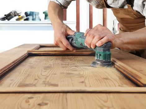 Türen streichen, Holztür, Handwerker schleift liegende Holztür mit Vibrationsschleifer ab, Foto: Visivasnc / iStock