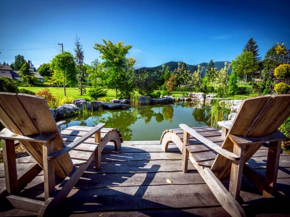 Schwimmteich, eine Terrasse, im Hintergrund ein Schwimmteich vor Bergpanorama. Foto: Daniel Vincek / Sstock.adobe.com