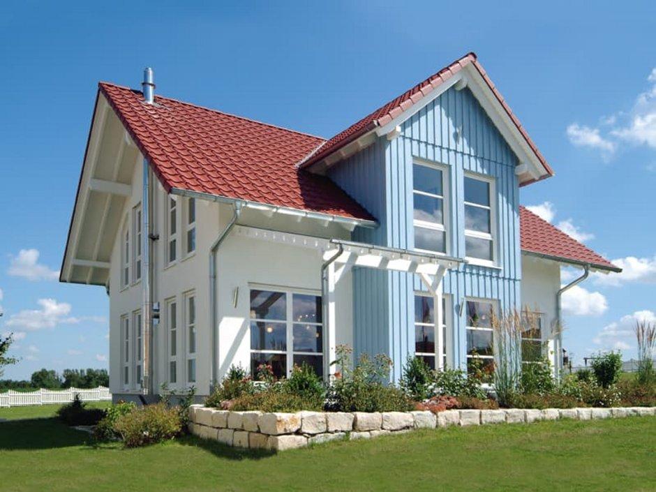 Holzständerbauweise, Haus mit blauem Zwerchhaus mit Holzfassade, der Rest ist weiß verputzt. Foto: Fertighaus Weiss