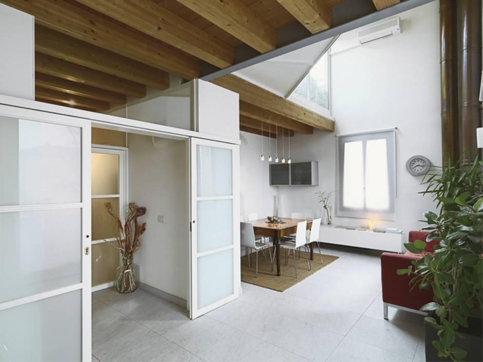 Innentüren, Schiebetür, Wohn- und Esszimmer mit hohen Decken, eine weiße Glasschiebetür steht zum Windfang hin offen. Foto: adpePhoto / stock.adobe.de