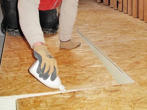 Fußbodendämmung, jemand verlegt OSB-Platten auf Dämmplatten, Foto: IVPU e.V.