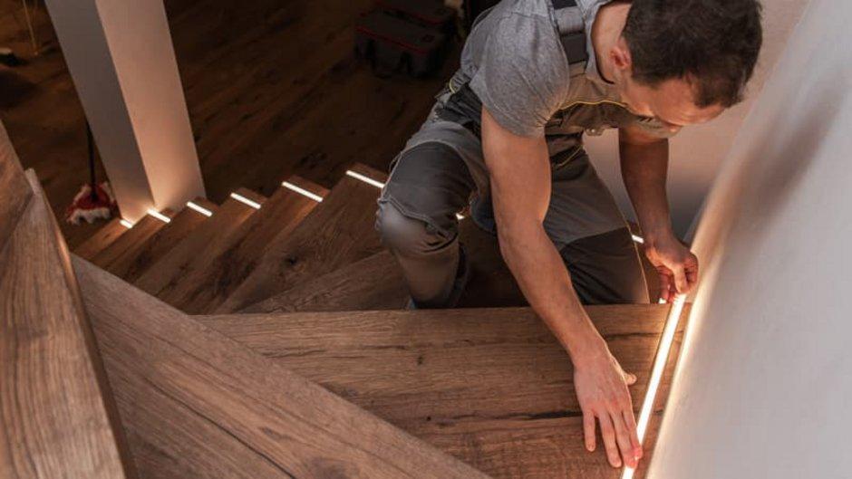 Beleuchtung, Handwerker klebt Leuchtstreifen auf Treppenstufen, Foto: Thomasz Zajda