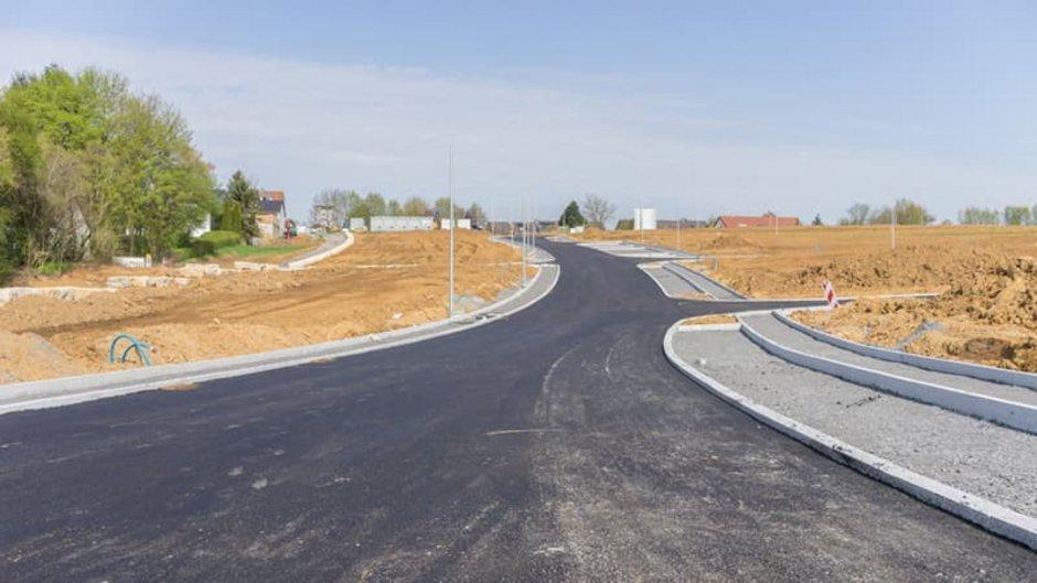 Grundstücksbewertung, Blick die Straßenflucht eines unbebauten Neubaugebiets entlang, Foto: ThomBal / stock.adobe.com