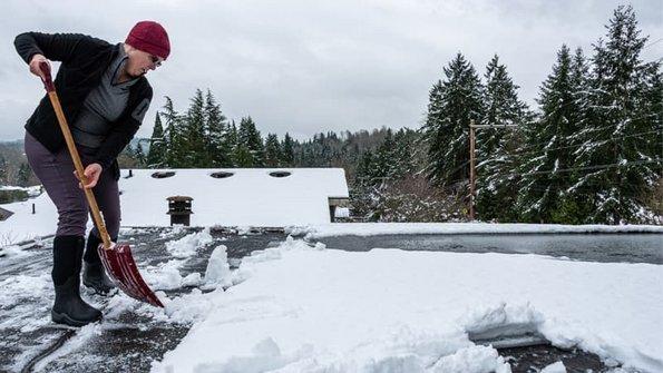 Flachdachhaus, eine Frau schippt auf einem Flachdach Schnee, Foto: knelson20 / stock.adobe.com