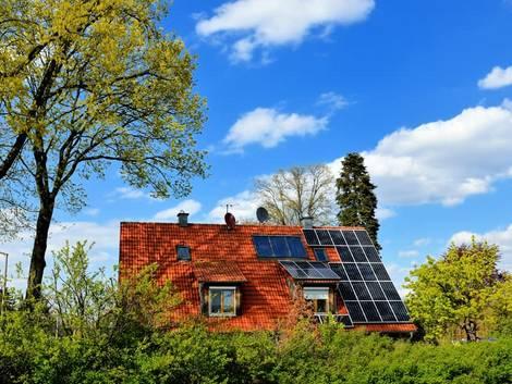Ökohaus, Bäume werden Schatten auf ein Dach und die dort installierte Photovoltaik-Anlage. Foto: reimax16/ Adobe stock