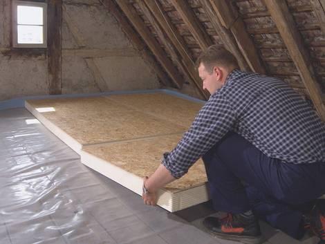 Fußbodendämmung, Mann verlegt Dämmplatten auf dem Dachboden, Foto: IVPU e.V.