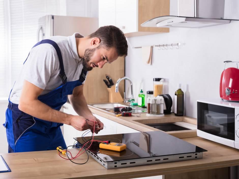 Gleichstrom, Wechselstrom, ein Elektriker schließt einen Elektroherd an, Foto: Andrey Popov / stock.adobe.com