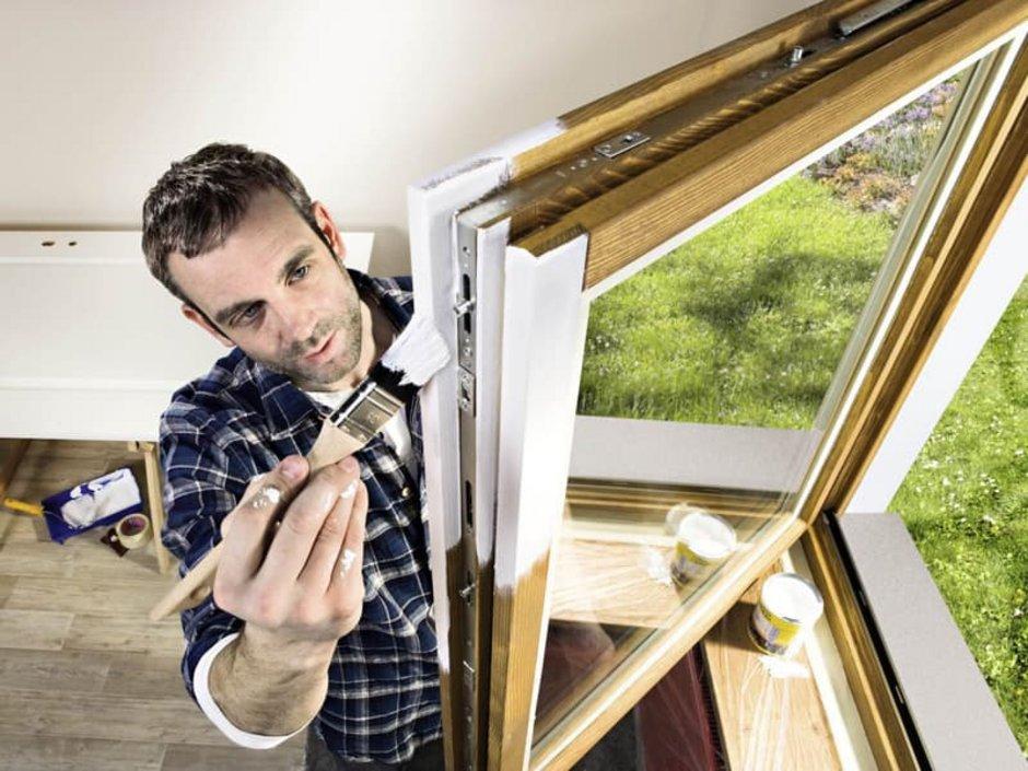 Holzfenster streichen, Foto von oben auf einen Mann, der sein Holzfenster weiß streicht, Foto: Hornbach