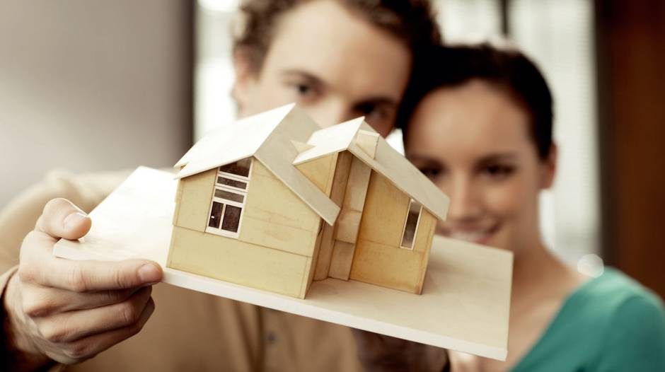 Kaufnebenkosten, ein Paar hält Modellhaus in die Kamera, Foto: djd/Deutsche Vermögensberatung