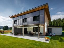 Ökohaus, ein Gebäude aus Holz, dessen Fassade zum Großteilaus Photovoltaik-Anlagen besteht. Foto: a2l/adobe stock