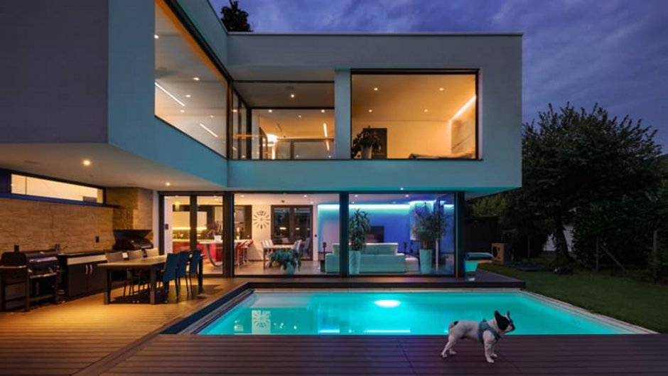 Beleuchtung, Haus bei Nacht, im Vordergrund der beleuchtete Pool, im Hintergrund Terrasse und Haus. Foto: iStock.com / piovesempre