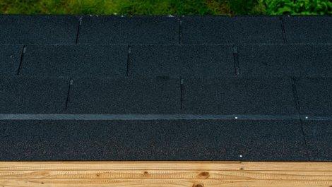 Dachpappe, Gartenhausdach  von oben, zu sehen ist der Holzuntergrund, die Dachpappe und ein schmaler Streifen Rasen. Foto: LitterART / stock.adobe.com